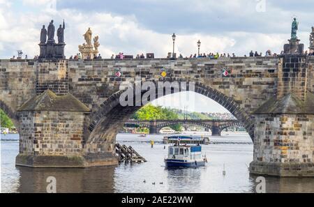 Tourist boat Adria passing under Gothic arches of Charles Bridge over Vltava Bridge Prague Czech Republic.