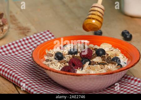 Pour honey in the morning healthy breakfast in a brown orange muesli dish, oat flakes, dried fruits with blueberries and raspberries - Stock Photo