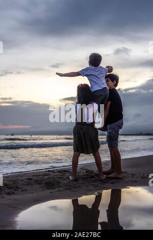 Three kids playing on the beach at sunset - Stock Photo