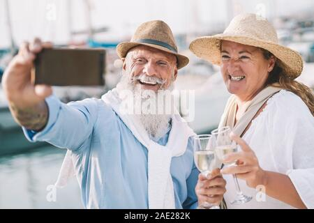 Seniors couple taking selfie with mobile smartphone on sailboat vacation - Happy people having fun celebrate drinking champagne on boat trip - Stock Photo