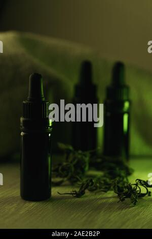 Vertical composition of three 10 ml black glass bottles surrounded with dried herbs on white wooden table backlit with green light - Stock Photo
