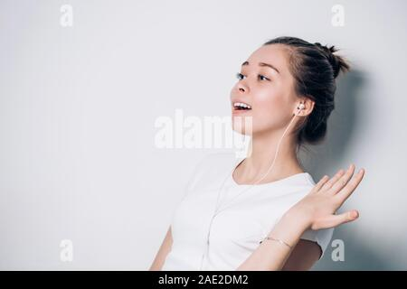 Enjoying the sound. Portrait of happy young woman with white earphones is listening music. Positive emotions, expressive facial features - Stock Photo