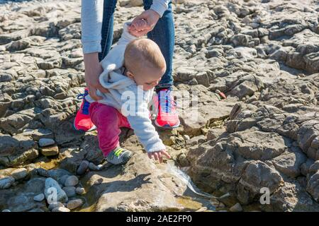 Cute blonde baby girl exploring beach in a sunny weather. - Stock Photo