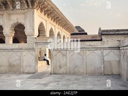 AGRA, Uttar Pradesh, India – February 25, 2015: A portrait of a security guard sitting inside the entrance of the ancient Agra Fort built by the Mugha - Stock Photo