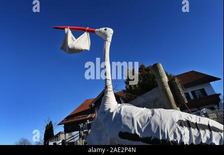 Buching, Germany. 06th Dec, 2019. A homemade stork figure with a bag in its beak symbolizes the birth of a baby in front of a farm. Credit: Karl-Josef Hildenbrand/dpa/Alamy Live News - Stock Photo