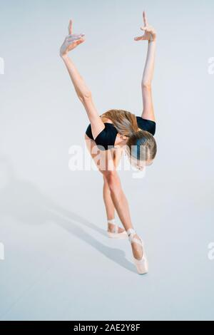 Professional ballerina dancing ballet on white cyclorama.Beautiful young girl with long hair wearing black suit isolated on white studio background. - Stock Photo