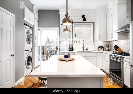 A luxurious white kitchen with stainless steel appliances and light colored wood floors. The view shows a winter scene. - Stock Photo