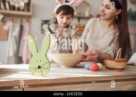 Conception of the easter. Mother and daughter in bunny ears have some fun in the kitchen at daytime - Stock Photo