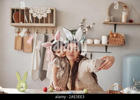 Taking selfie. Mother and daughter in bunny ears at easter time have some fun in the kitchen at daytime - Stock Photo