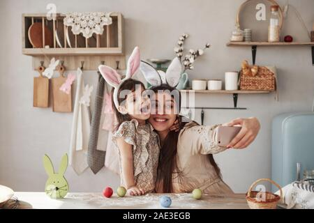 Making funny faces. Mother and daughter in bunny ears at easter time have some fun in the kitchen at daytime - Stock Photo