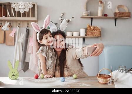 Using white colored smartphone. Mother and daughter in bunny ears at easter time have some fun in the kitchen at daytime - Stock Photo