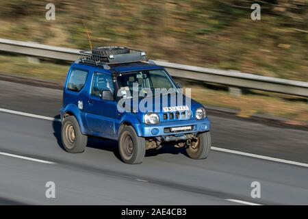 Blurred moving car Suzuki Jimny Jlx traveling at speed on the M61 motorway; Slow camera shutter speed exaggerating vehicle movement - Stock Photo