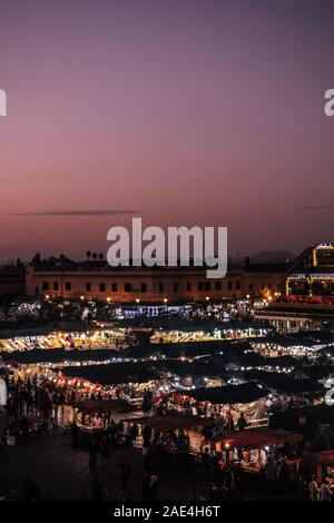Djemaa el Fna main market place in Marrakech, Morocco while sunset - Stock Photo