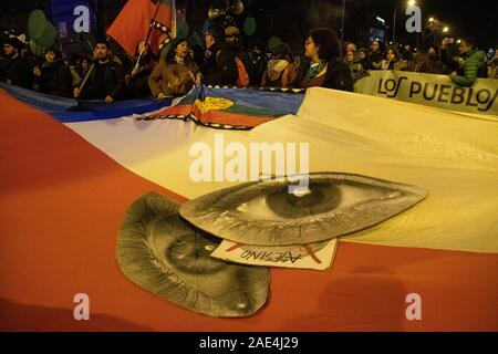 Madrid, Spain. 6th December, 2019. A gigant flag of Chile with two eyes in the middle, representing the eyes lost by the demonstrators during the protests in Chile, during the rally for the climate emergency held in Madrid. © Valentin Sama-Rojo/Alamy Live News. - Stock Photo