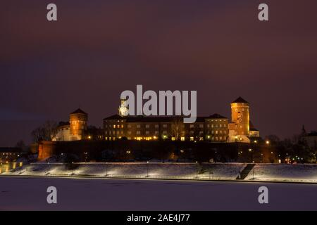 Night view of historic royal Wawel Castle in Cracow, Poland, and frozen Vistula river during winter - Stock Photo