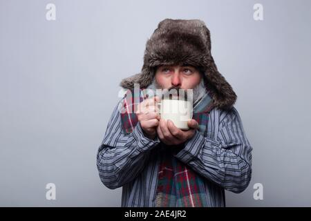 Man suffering from influenza with pajamas and with a cap blowing a cup of hot tea to warm up on a gray background. Health concept. - Stock Photo