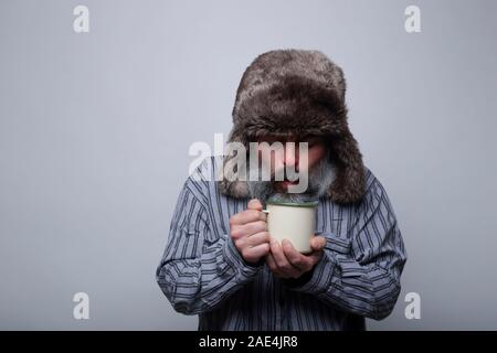 Flu sick man with pajamas and with a cap blowing a cup of hot tea on a gray background. Health concept. - Stock Photo