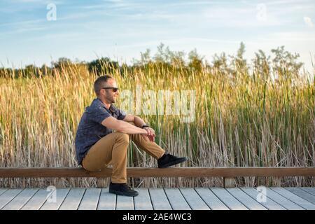 Side view of a peaceful man sitting on boardwalk in park in sunlight