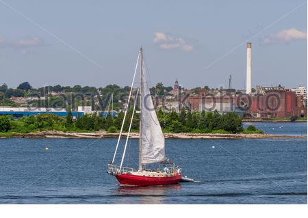 New Bedford, Massachusetts, USA - July 26, 2019: Sailor guiding sailboat out of New Bedford inner harbor - Stock Photo