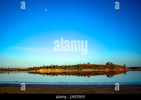Bushland is reflected in the still waters of pink lake under a daytime full moon at dawn in Murray-Sunset National Park, in southern Australia - Stock Photo
