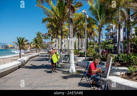 Street artist and surfer on the Puerto Vallarta malecon, a popular tourist zone in the Mexican city, with palm trees and Pacific Ocean beach. - Stock Photo