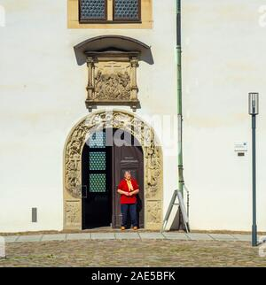 Caucasian woman standing in portal to Castle Hartenfels chapel the first Protestant church in the world Altstadt Torgau Saxony Germany. - Stock Photo