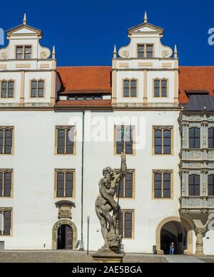 Stone statue of Neptune in fountain in front of the portal to Castle Hartenfels chapel the first Protestant church in the world Torgau Saxony Germany. - Stock Photo