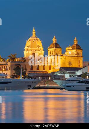 Dusk view of boats moored alongside the historic buildings of the walled old city of Cartagena in Colombia.