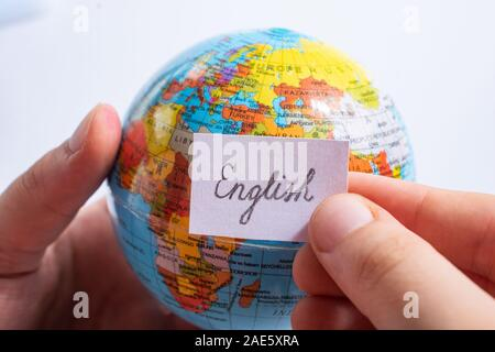 Hand holding notepaper with English wording on model globe - Stock Photo