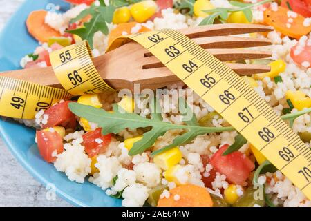 Fresh prepared salad with couscous and vegetables. Healthy light dietary vegan meal for slimming - Stock Photo