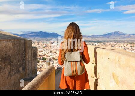 Tourism in Alicante, Spain. Back view of traveler girl walking on Santa Barbara castle enjoying view of Alicante city, Spain. Young female backpacker - Stock Photo