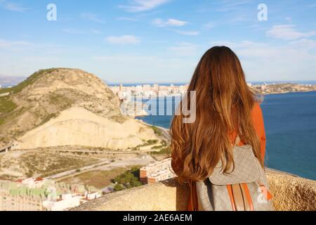 Back view of traveler girl enjoying view of Alicante city from Santa Barbara castle, Spain. Young female backpacker relaxing in her travel in southern - Stock Photo