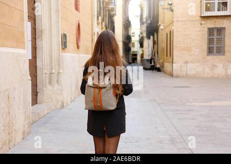 Young tourist woman walking in the street. Female backpacker traveling in Europe in autumn or winter time. - Stock Photo