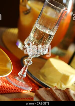 close up breakfast table with champagne, natural light on glass - Stock Photo