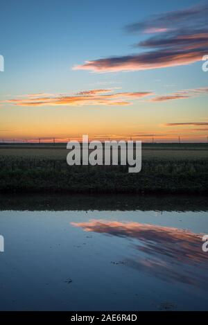 Colorful sunlit altocumulus clouds over a small lake in the dutch countryside at sundown. Beautiful reflections in the water of the lake. - Stock Photo