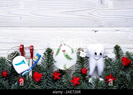 Cute cartoon tooth with toothbrush and dental floss on sled christmas background with decorations on white wooden board. Top view, flat lay. - Stock Photo