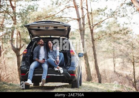 Laughing and having nice time. Sitting on rear part of automobile. Enjoying the nature. Couple have arrived to the forest on their brand new black car - Stock Photo