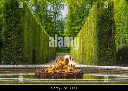 Gorgeous view of the Saturn Fountain, an allegory of Winter, with an alley of tall geometrical formed topiaries in the background in the Gardens of... - Stock Photo