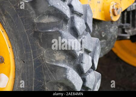 Up close view of tire on large yellow tractor. - Stock Photo