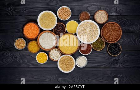 Cereals, grains, seeds and groats black wooden background - Stock Photo