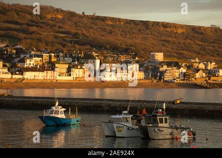 Inshore fishing boats and other vessels moored in Lyme Regis harbour in early December. Lyme Regis is situated on the heritage coast or jurassic coast - Stock Photo