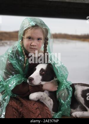 A child and a dog in a flood disaster area. The girl was crying, soaked in the rain - Stock Photo