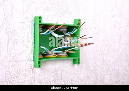 Electrical panel of a distribution box or junction box with protruding ends of bare copper wires. Household electric installation work, home wiring re - Stock Photo