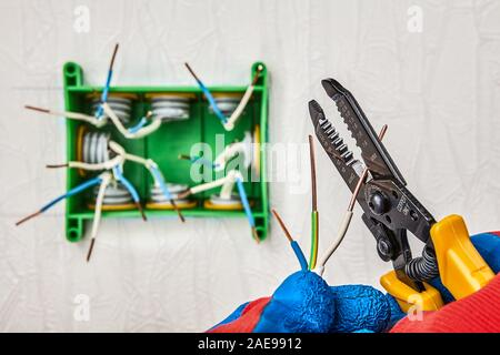 Ends of exposed copper wires protruding out junction box in the stage of installation. An Electrician cutters part of wire with use cutter tool. Repai - Stock Photo