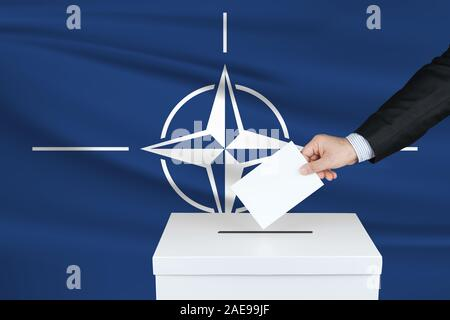 Election in North Atlantic Treaty Organization. The hand of man putting his vote in the ballot box. Waved North Atlantic Treaty Organization flag on b - Stock Photo