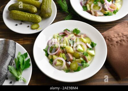 Herring salad with potato, onion, marinated cucumber and apple on wooden table. - Stock Photo