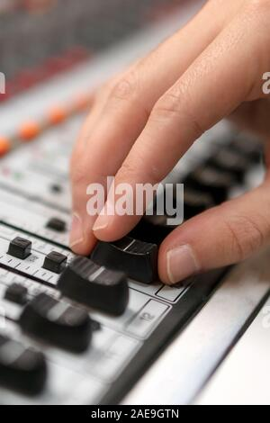 Male hand on control Fader on console. Sound recording studio mixing desk with engineer or music producer . - Stock Photo