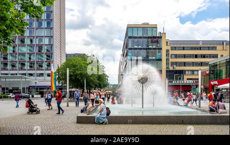 People sitting around fountain and pond in shopping mall in central Dresden Saxony Germany.
