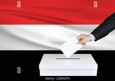 Election in Yemen. The hand of man putting his vote in the ballot box. Waved Yemen flag on background. - Stock Photo