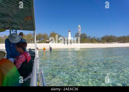 Lady elliot Island Australia - November 25 2019; People on board dive boat while others are entering and leaving water with lighthouse and beach backg - Stock Photo